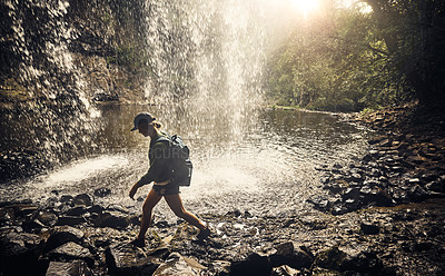 Buy stock photo Shot of a young woman walking on a rocky surface by a waterfall in nature