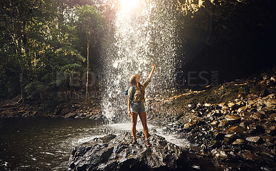Buy stock photo Shot of a young woman taking a selfie by a waterfall in nature
