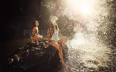 Buy stock photo Shot of two young woman looking up at a waterfall enjoying a day in nature