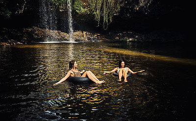 Buy stock photo Shot of two young female friends enjoying water by a waterfall in the forest