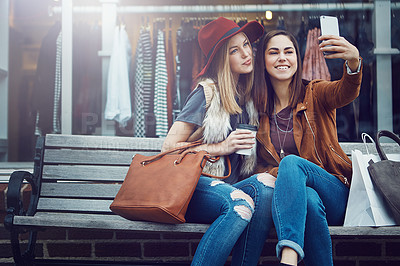 Buy stock photo Cropped shot of two young girlfriends snapping selfies while sitting on a bench during a shopping spree