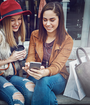 Buy stock photo Cropped shot of two young girlfriends sending text messages while sitting on a bench during a shopping spree