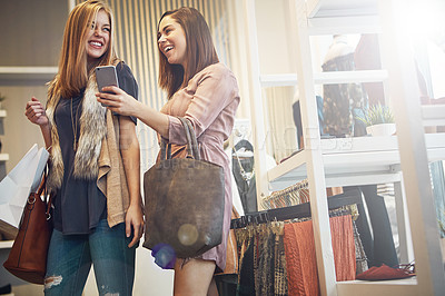 Buy stock photo Shot of best friends looking at a cellphone while out on a shopping spree