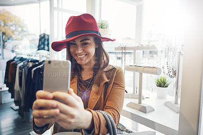 Buy stock photo Cropped shot of an attractive young woman snapping selfies while out on a shopping spree