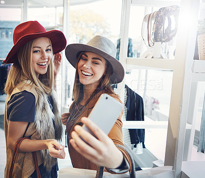 Buy stock photo Cropped shot of two young girlfriends snapping selfies while out on a shopping spree