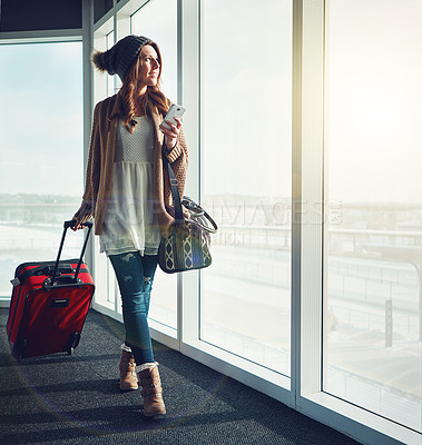 Buy stock photo Shot of a young woman standing at an airport with her luggage staring outside while holding her cellphone
