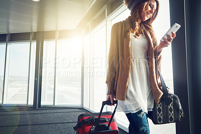 Buy stock photo Shot of a young woman walking in an airport with her luggage while looking at her cellphone