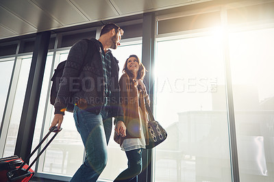 Buy stock photo Shot of a young couple walking in anairport with their luggage while holding hands and looking at each other