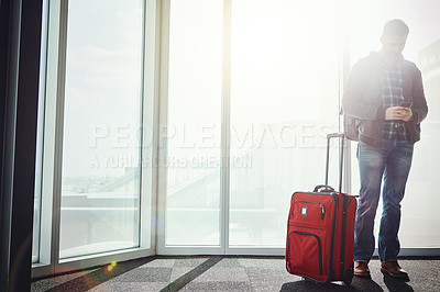 Buy stock photo Shot of a young man standing in an airport with his luggage while looking at his cellphone and texting