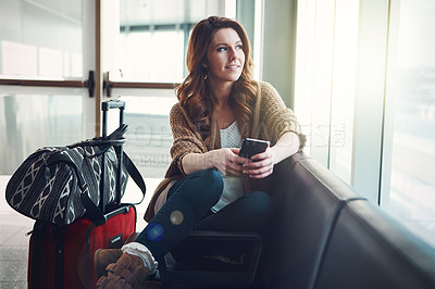 Buy stock photo Shot of a young woman sitting in an airport with her luggage and holding her phone while looking outside