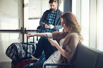 Buy stock photo Shot of a young couple sitting in an airport with their luggage while making use of their cellphones