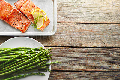 Buy stock photo Shot of a dish with fish and a plate of asparagus on a table