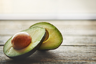 Buy stock photo Shot of a sliced avocado on a table