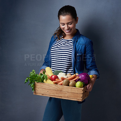 Buy stock photo Studio shot of a beautiful young woman holding a wooden crate full of fruit and vegetables against a blue background