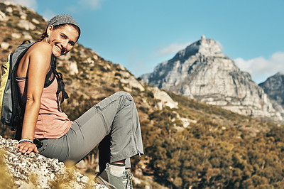Buy stock photo Portrait of a young woman taking a break while out on a hike through the mountains