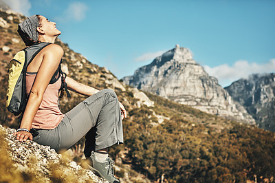 Buy stock photo Shot of a young woman taking a break while out on a hike through the mountains