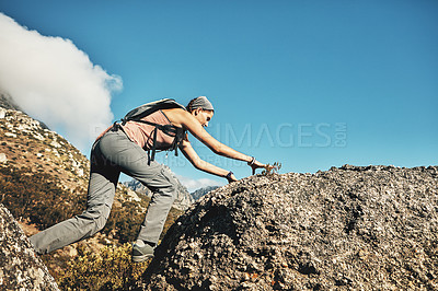 Buy stock photo Shot of a young woman climbing over rocks while out on a hike through the mountains