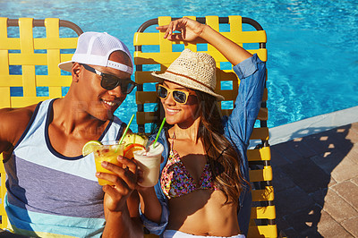 Buy stock photo High angle shot of an affectionate young couple enjoying a few drinks poolside