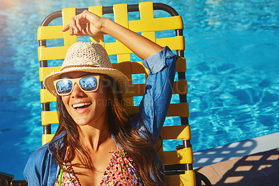 Buy stock photo High angle shot of an attractive young woman catching some sun by the pool