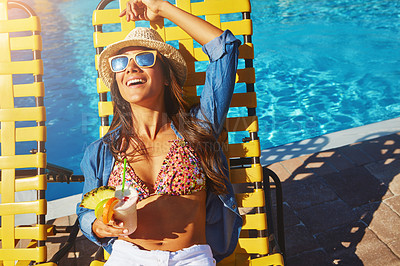 Buy stock photo High angle shot of an attractive young woman enjoying a drink by the pool