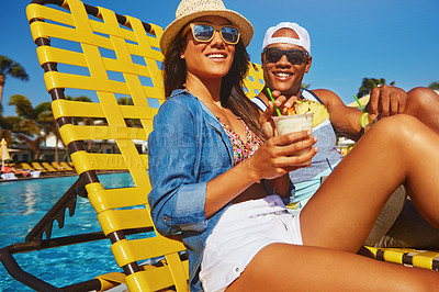 Buy stock photo Cropped shot of an affectionate young couple enjoying a few drinks poolside