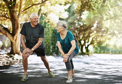 Buy stock photo Shot of a senior couple warming up before a run outside
