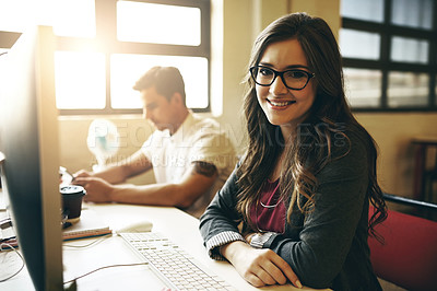 Buy stock photo Cropped portrait of an attractive young woman working alongside a male colleague in their office