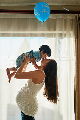 Buy stock photo Shot of a pregnant woman playing with her little boy in her bedroom at home