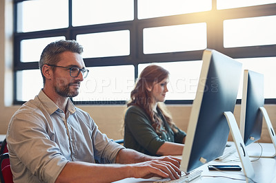Buy stock photo Shot of two designers working on computers in an office