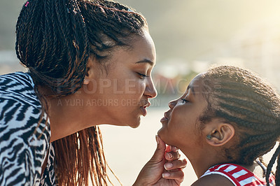 Buy stock photo Shot of a mother giving her little daughter a kiss at the beach