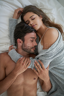 Buy stock photo High angle shot of a happy young couple cuddling together in bed