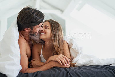Buy stock photo Shot of an affectionate young couple laying under a duvet together in bed