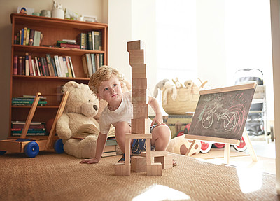 Buy stock photo Shot of an adorable little boy playing with wooden blocks at home