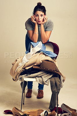 Buy stock photo Studio shot of a young woman choosing clothing piled on a chair against a brown background
