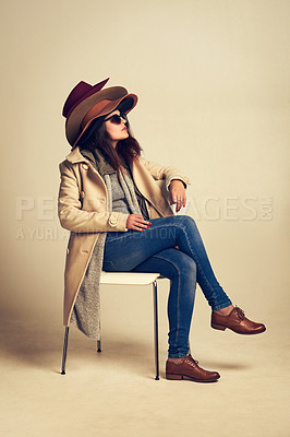 Buy stock photo Studio shot of a young woman sitting on a chair and wearing a pile of hats against a brown background