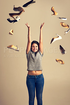 Buy stock photo Studio shot of a joyful young woman throwing a bunch of shoes in the air against a brown background