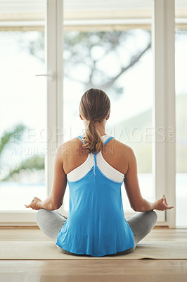 Buy stock photo Rearview shot of a young woman practicing yoga at home