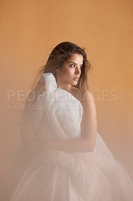 Buy stock photo Portrait of a beautiful young woman covering herself with a ballet skirt in studio