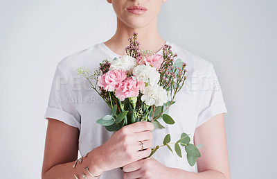 Buy stock photo Studio shot of an unrecognizable woman holding a bunch of flowers against a grey background