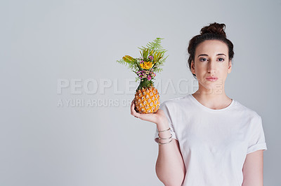 Buy stock photo Studio shot of a beautiful young woman holding a pineapple against a grey background