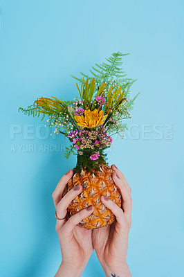 Buy stock photo Shot of an unrecognizable woman holding a pineapple stuffed with flowers