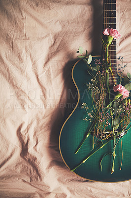 Buy stock photo High angle shot of a green guitar lying on a bed with flowers arranged on it