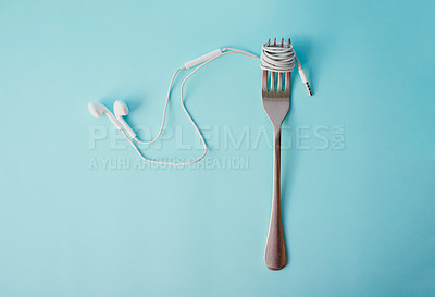 Buy stock photo Studio shot of earphones wrapped around a fork against a blue background