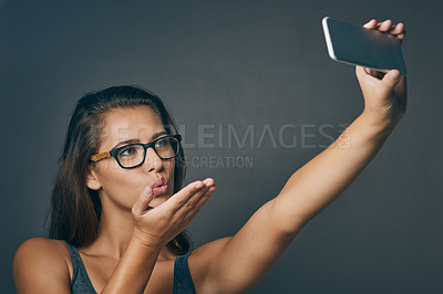 Buy stock photo Studio shot of an attractive young woman taking a selfie against a grey background