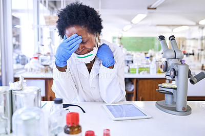 Buy stock photo Shot of a female scientist looking stressed out while working in a lab
