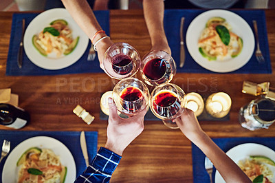 Buy stock photo Shot of a group of unrecognizable people toasting at the dining room table at home