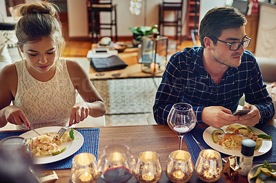 Buy stock photo Shot of young couple enjoying a meal at the table