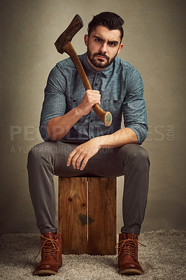 Buy stock photo Studio shot of a young man posing with an axe against a green background