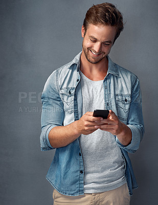 Buy stock photo Shot of a happy young man using his smartphone while standing against a gray background in the studio