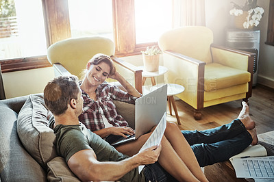 Buy stock photo Shot of a young couple using a laptop and going through paperwork together on the sofa at home